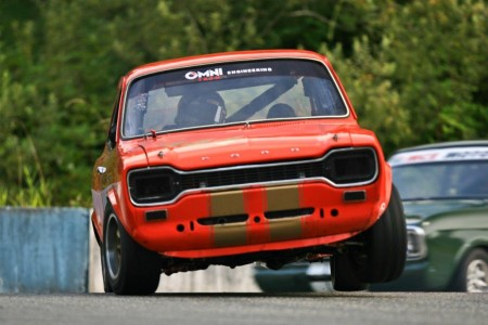 John McCoy (1969 Ford Escort Twin Cam) gets two wheels in the air rounding Mission's Turn 3 attempting to stay ahead of Alan McColl in his Ford Lotus Cortina. - Tony Ioannou photo