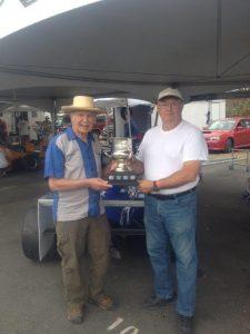 Lorne Andras (L) accepts 'The Battered Cup' on behalf of Steve Clark from Canadian motorsport legend and Hall of Famer, Bill Sadler. - VRCBC photo